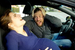 Pregnant woman screaming in car feeling pain with shouting husband Royalty Free Stock Images