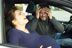 Pregnant woman screaming in car for pain husband scared Stock Photos