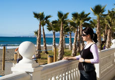 Pregnant woman at sea. Pregnant woman looking at sea in her sunglasses by white fence royalty free stock images