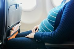 Pregnant woman traveling by plane stock photo