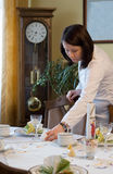 Pregnant woman setting table. For Easter Eve meal royalty free stock photography