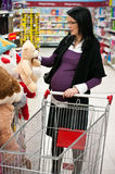 Pregnant woman shopping. Closeup of pregnant woman shopping in supermarket with trolley cart and teddy bear in hand Royalty Free Stock Photography