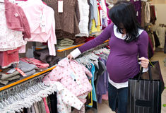 Pregnant woman shopping. A pregnant woman shopping for baby clothes Stock Photos