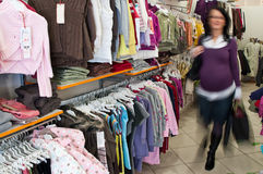 Pregnant woman shopping. A pregnant woman in shop, walking past hangers, motion blurred Royalty Free Stock Photos
