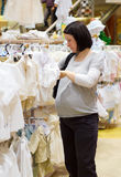 Pregnant woman shopping. For baby clothes stock images