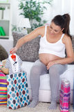 Pregnant woman shopping baby clothes Stock Photography