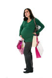 Pregnant woman with shopping bags. Beautiful Caucasian pregnant brunette woman holding shopping bags while standing expressing pain and holding belly as if her Royalty Free Stock Images
