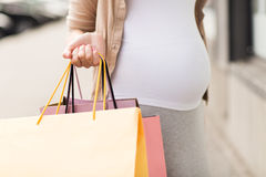 Pregnant woman with shopping bags at city Stock Images
