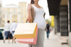 Pregnant woman with shopping bags at city street Stock Photo