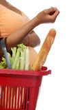 Pregnant woman with shopping basket Stock Images