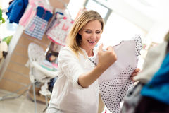 Pregnant woman shopping clothes for her baby. Beautiful pregnant woman in white shirt shopping clothes for her baby royalty free stock images