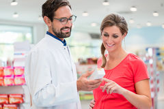 Pregnant woman shopping in drug store. Pregnant women shopping in drug store being advised by sales man Stock Photography