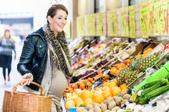 Pregnant woman shopping groceries on farmers market royalty free stock photos