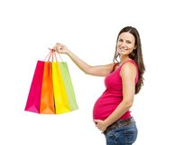 Pregnant woman shopping isolated on white. Studio portrait of beautiful young pregnant woman with shopping bags, isolated on white background Royalty Free Stock Images