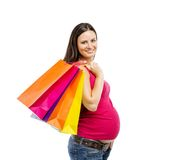 Pregnant woman shopping isolated on white. Studio portrait of beautiful young pregnant woman with shopping bags, isolated on white background Stock Images