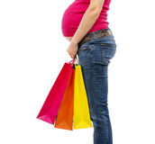 Pregnant woman shopping isolated on white. Studio portrait of beautiful young pregnant woman with shopping bags, isolated on white background Royalty Free Stock Photo