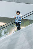Pregnant woman on shopping mall escalator, Beijing, China. BEIJING-MAY 18, 2016. Pregnant woman on shopping mall escalator. China is concerned over an aging Royalty Free Stock Image