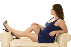 Pregnant woman in a short blue dress sitting legs up on couch royalty free stock photography