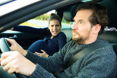 Pregnant woman shouting to scared husband in car Stock Images