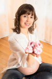 Pregnant Woman Showing Baby Clothes Royalty Free Stock Photography