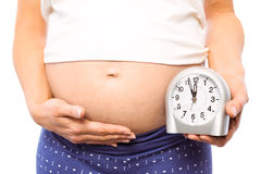 Pregnant woman showing clock and bump Royalty Free Stock Images