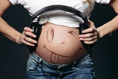 Pregnant woman showing her naked tummy with smile and holding earphones. Close up of pregnant lady wearing white t-shirt, holding black earphones on tummy royalty free stock photos