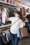 Pregnant woman showing her purchases in children's clothes sho Stock Photo