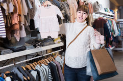 Pregnant woman showing her purchases in children's clothes sho Royalty Free Stock Photo