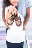 Pregnant woman showing shoe. Close-up of pregnant women showing shoes at home Royalty Free Stock Image