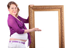 Pregnant woman shows large carved frame Stock Images