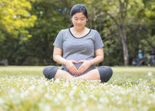 Pregnant woman sit on the ground carry her belly with love sign. Royalty Free Stock Image
