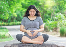 Pregnant woman sit on wood with love hand sign. Stock Photos