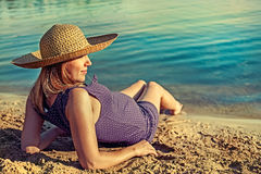 Pregnant woman sits on the beach. Pregnant woman relaxing on the beach Royalty Free Stock Photography