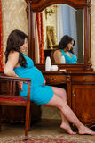 Pregnant woman sits before dressing table. Stock Image