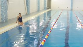 A pregnant woman sits on the edge of the pool. Young pregnant woman doing sports in the pool. Wide shot stock video