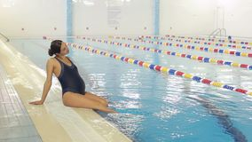 A pregnant woman sits on the edge of the pool. Young pregnant woman doing sports in the pool. Wide shot stock footage