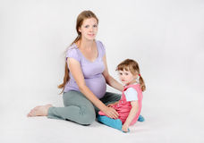 Pregnant woman sits on floor with daughter Royalty Free Stock Photography