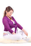 Pregnant woman sits on fur and looks at belly Royalty Free Stock Photos