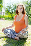 Pregnant woman sits on grass Stock Photo