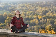 Pregnant woman sits on a hill with her eyes closed. Meditation. royalty free stock photo