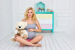 Pregnant woman sits and holds a teddy bear Stock Image