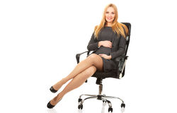 Pregnant woman sitting on armchair Stock Images