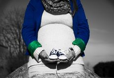 Pregnant woman sitting with baby shoes in front of herself Stock Photos
