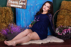 Pregnant woman is sitting with basket of flowers Royalty Free Stock Photos