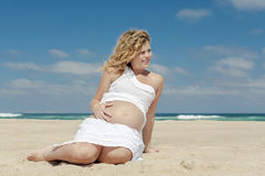 Pregnant woman sitting on the beach Royalty Free Stock Photography