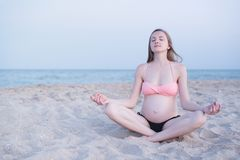 Pregnant woman sitting on a beach and meditates. Soft evening light, deserted beach royalty free stock images