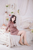 Pregnant woman sitting on a bed Stock Photography