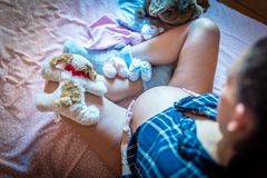 Pregnant Woman on Bed Caressing her Tummy. Toys and Shoes Around stock image