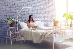 Pregnant woman sitting on bed with laptop, having breakfast Royalty Free Stock Photography