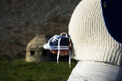 Pregnant woman sitting on a bench with baby shoes Stock Image
